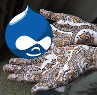 hands covered in henna patterns, holding the Drupal icon